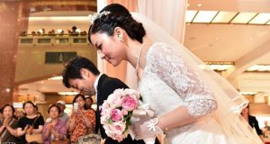 Bride Rie Oka (R) and her father Kazuyoshi Oka (L) arrive for a wedding ceremony at the Mitsukoshi department store in Tokyo on August 8, 2015. Mitsukoshi and bridal service company Minnano-wedding produced a non-religious wedding ceremony before some 500 shoppers at the department store.  AFP PHOTO / Yoshikazu TSUNO        (Photo credit should read YOSHIKAZU TSUNO/AFP/Getty Images)