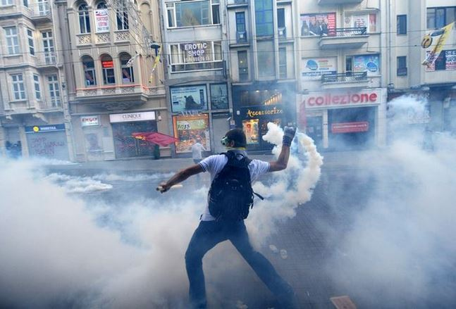 A protestor throws back a canister of tear gas to Turkish riot policemen during a protest against the demolition of Taksim Gezi Park on May 31, 2013, at Taksim in Istanbul. Police reportedly used tear gas on early May 31 to disperse a group, who were standing guard in Gezi Parki to prevent the Istanbul Metropolitan Municipality from demolishing the last remaining green public space in the center of Istanbul as a part of a major Taksim renewal project. TOPSHOTS/AFP PHOTO/BULENT KILIC